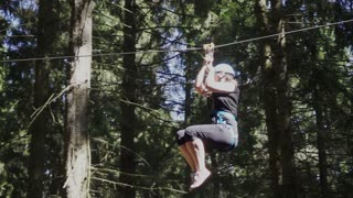 Young woman in protective helmet and belt moving on rope with carbine on high in extreme park. Extreme descend on rope between trees in climbing park