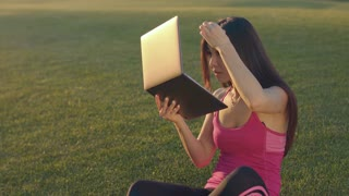 Young woman looking in laptop as in in mirror. Asian woman with laptop sitting on grass. Sport girl touching her hair. Smiling woman with laptop on green meadow. Sport woman laptop grass