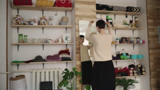 Young woman looking in mirror and touching hair in small store. Creative woman fitting jumper in knitting workshop