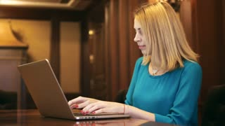 Young woman looking on screen laptop and typing on keyboard. Blonde woman using notebook computer for browsing internet in luxury interior