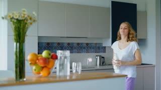 Young woman preparing oatmeal porridge in kitchen. Girl puts bottle of milk and oatmeal on table. Beautiful girl preparing healthy breakfast in morning. Cooking woman in modern kitchen interior