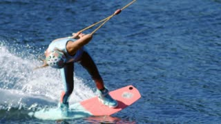 Young woman riding wakeboard board on summer river. Entertainment on water river. Waterskier moving fast in splashes of water. Girl wakeboarder riding on river splashing of water. Extreme lifestyle