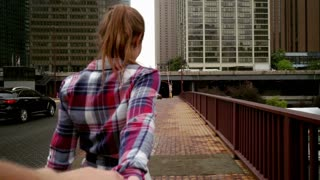 Young woman showing great view of modern city skyscrapers. Follow me concept. Travellers walking city street in cityscape. Man follow by girlfriend in Chicago city. Tourist couple