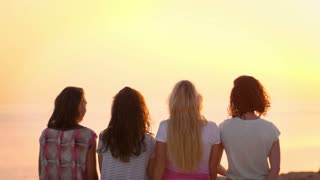 Young woman showing love sign at sunset. Woman friends enjoy summer vacation. Summer women showing word love with hands. Back view of girls friends relaxing on sunset