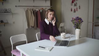 Young woman sitting at table and talking by mobile phone. Business woman calling on mobile and write note in notebook. Female manager using laptop at table in workshop