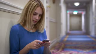 Young woman sitting on floor leaning on wall in long corridor and using mobile phone. Beautiful woman looking smartphone sitting on floor in hallway corridor. Attractive girl chatting on phone
