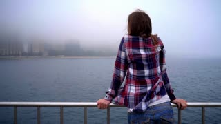 Young woman standing on embankment of sea. Back view of woman enjoying life. Beautiful woman standing back. Girl looking away city. Dreaming concept. Back girl standing and looking sea city