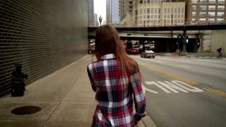 Young woman talking on smart phone in modern city. Back view of woman in casual dress walking and talking on mobile phone. Urban city lifestyle. Woman walking in street chicago