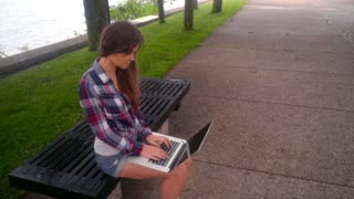 Young woman typing laptop. Beautiful woman with laptop sitting on bench at park. Inspired woman woman working on laptop in park. Girl using laptop outside