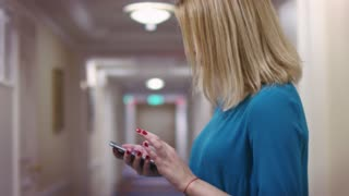 Young woman using smartphone screen for surfing in internet. Blonde woman browsing new mobile app on smartphone in hotel interior. Blonde girl chatting on phone