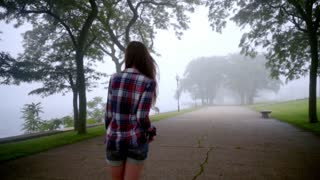Young woman walking in park fog. Beautiful brunette woman going in empty park. Walking woman back view. Walking girl in fog trees. Back view of woman in denim shorts walking at park