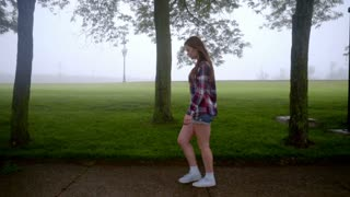 Young woman walking in park. Walking woman in casual dress. Beautiful brunette girl walking in park fog. Profile view of walking girl in park. Alone woman walk at green park