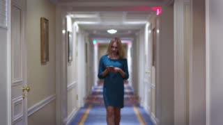 Young woman walking on long corridor on hallway and looking on screen smartphone. Woman walking in hotel corridor and using mobile phone. Elegant woman