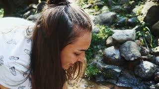 Young woman washing face in spring water. Close up beautiful wet woman face with water drops