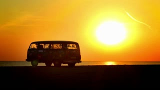 Volkswagen minibus on sea sunset background.
