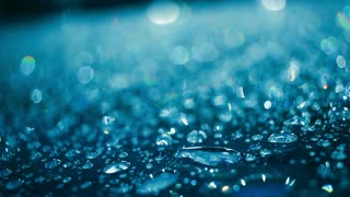 Water drops on glass after rain. Water droplets on glass in blue color. Shiny droplets. Shimmering drops on glass at night. Abstract background. Droplet background. Rain drops on glass surface