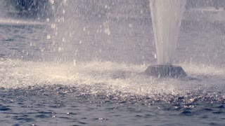 Water fountain in slow motion. Splashing streams of water fountain. Water streams splashing on water surface. Fountain water splash. Powerful water jet. Closeup of drops fall on water surface