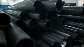 Gas pipes closeup. Stack of black metal pipes. Stack of metal tubes at industrial warehouse. Heavy industry products. Industrial background