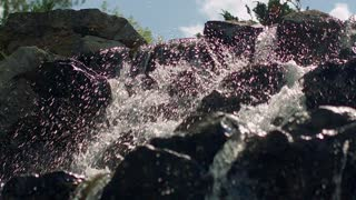 Water splashes in slow motion. Closeup of waterfall. Splashes of water in sunlight. Water falling over rocks in slow motion. Mountain waterfall. Water splashing on stones. Water rushing over stones