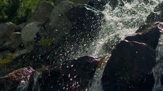 Water splashes in sunlight. Closeup of water splashing in slow motion. Waterfall splashing over stones. Water splash. Water falling over stones. Mountain waterfall. Water splashing on stones
