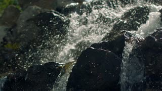 Water splashing in slow motion. Closeup of waterfall in mountain. Cascading water. Water splashes. Close up of waterfall rocks. Water streams in sunlight. Water falling over stones