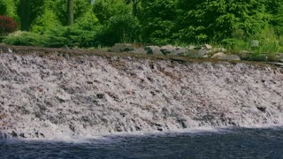 Water stream falling down over stone cascade. Waterfall in slow motion. River water flowing down over stone cascade. River waterfall in slow motion. Water fall in summer park. Water flowing in garden