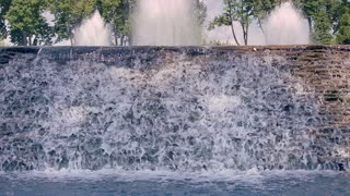 Waterfall closeup. River waterfall. Water falling down over stone cascade in slow motion. Water streams splashing at water surface. Water fountains. Water flowing over rocks cascade