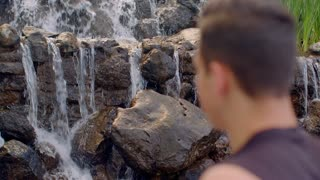 Waterfall relaxation. Man relaxing at morning. Relaxation concept. Young man standing looking at waterfall outdoor. Closeup of man looking waterfall. Back view man looking waterfall