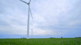 Wind generator at cloudy weather. Wind generator on green field. Sustainable energy resource. Wind generator on farm field. Wind energy concept. Wind power generator