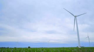 Wind power concept. Wind turbines field. Dolly shot of wind turbines generating electricity on green field. Alternative energy concept. Green power. Wind turbines on green field