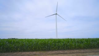 Wind power generator on green field. Green energy source. Wind turbine at cloudy weather. Alternative energy production. Renewable energy resource. Wind energy generation. Eco power concept