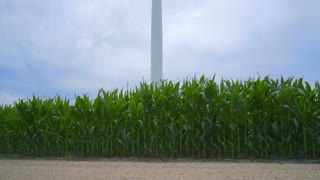Wind tower against cloudy sky. Closeup of wind turbine on corn field. Renewable energy resource. Wind generator on farm field. Alternative energy concept. Wind power generator