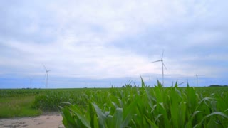 Wind turbine farm on green field. Wind turbines landscape. Clouds sky over wind generators. Wind turbine field. Wind power. Wind energy generation. Alternative energy resource
