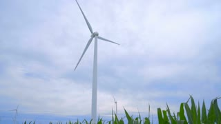 Wind turbine generating wind power. Wind turbine rotating in field on clouds sky background