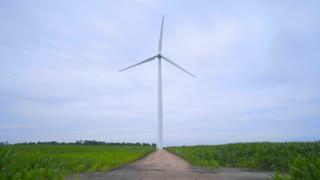 Wind turbine on wind farm. Wind generator. Wind power generation. Wind turbine generator standing on rustic road between farm fields. Renewable energy concept. Sustainable energy resource