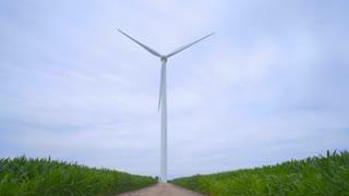 Wind turbine. Wind generator. Alternative energy concept. Wind turbine generator between green fields. Wind power station. Wind power plant. Windmill. Wind turbines farm