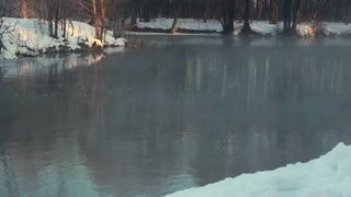Winter river. Mist over river in winter forest. Winter landscape. Winter river with fog. River bank covered with snow. Misty winter river. Snowy winter forest. Ripple on water surface. Cold weather