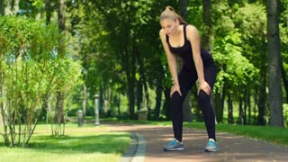 Woman breathing after run marathon outdoor. Tired female runner after running in park. Fitness woman relaxing after jogging. Slim girl resting after fitness workout. Fit girl breathing after training