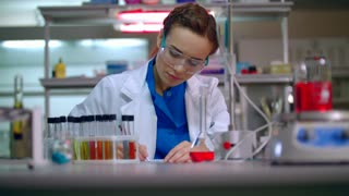 Woman chemist writing research data in lab. Lab worker pick up test tube rack. Chemist writing chemical research report. Female chemist working in chemical laboratory