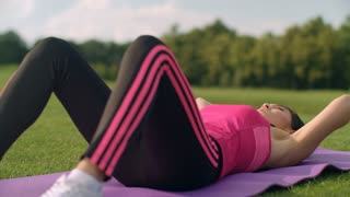Woman crunch exercise outdoor. Asian girl doing sit ups in park. Fitness woman workout for abdominal muscle. Fitness girl doing situps in slow motion. Close up of fitness woman doing sit up exercise