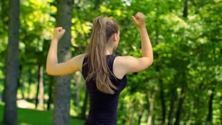 Woman doing fitness exercises in green park at spring. Closeup of female runner warm up muscles outdoor. Young woman stretching in park. Fit girl workout. Healthy lifestyle and wellness concept