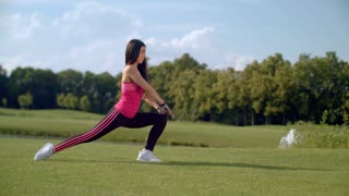 Woman doing legs stretching exercise outdoors. Asian woman stretching legs in park at sunny day. Fitness woman stretching legs before workout. Young woman stretching workout