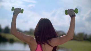 Woman lifting weights outdoor. Woman working on her shoulders. Fitness woman exercising with weights in arms. Back of woman exercising with dumbbells. Fitness workout outdoor