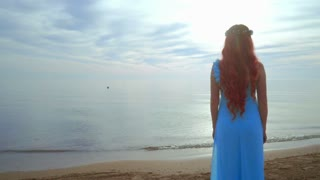 Woman on sea beach. Redhead woman looking at sea. Woman dreaming on sea beach. Blue dress. Girl standing near ocean. Woman beach. Dreaming concept. Dreaming woman. Woman sea. Rear view woman beach