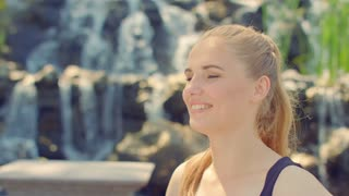 Woman posing in sunlight. Woman portrait outdoor. Caucasian woman looking at camera. Woman face. Blonde woman. Close up of young woman smiling on background of waterfall. Pretty girl posing in park