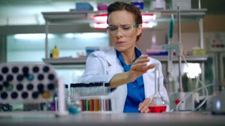 Woman researcher in lab. Research scientist working in research laboratory. Female researcher analyzing chemical liquid in laboratory glassware. Laboratory research concept. Researcher in laboratory