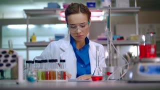 Woman researcher working in lab. Female researcher writing research report in modern laboratory. Woman scientist writing data report in research laboratory. Scientist woman working in chemical lab