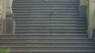 Woman running down stairs in slow motion. Running woman on staircase. African woman running down stairs. Running downstairs. Real girl jogging down stairway. Fitness workout outdoor