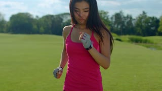 Woman running outdoor. Closeup of running woman in slow motion. Asian woman running in park. Fit girl run outdoors. Close up of fitness woman run on meadow. Female runner run at summer