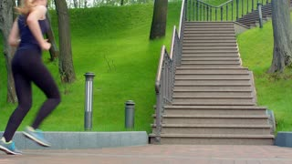 Woman running up stairs in slow motion. Real women run upstairs in park. Fit girl running up staircase at park. Sport life. Fitness exercising. Lifestyle concept. Young woman fitness workout outdoor